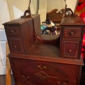 A dresser with an oval mirror.