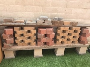 A low shelf on concrete blocks with other bricks stored above.
