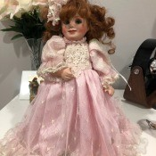Identifying a Porcelain Doll? - doll wearing a pink lace and ruffle trimmed dress