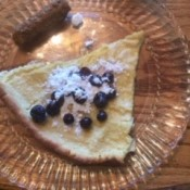 A plate containing a slice of Dutch Baby, with powdered sugar and blueberries on top.