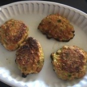 A plate with four vegetable fritters.