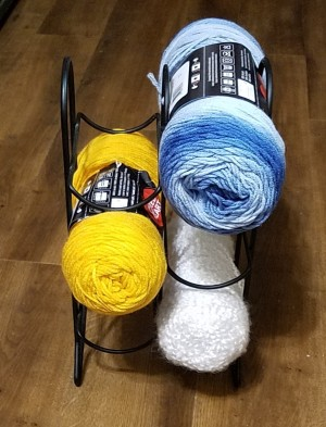 Three skeins of yarn in a wire wine rack.