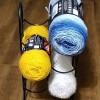 Three skeins of yarn in a wire wine rack.