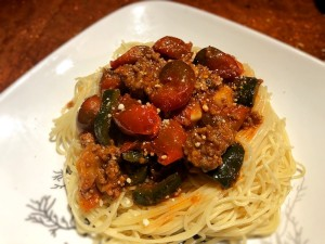 A plate of pasta topped with cherry tomato bolognese.