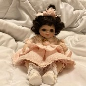Identifying a Porcelain Doll? - small dark haired doll wearing a pink dress