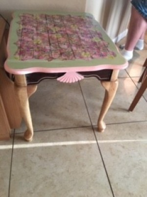table painted pink and light green with a decorative vinyl top