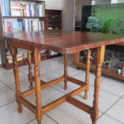A wooden gate leg drop leaf table.