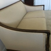 A white couch with wooden trim.
