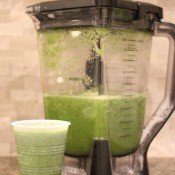 The blended green juice in a blender and in a cup.