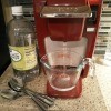 Vinegar and water in front of a Keurig coffee machine.