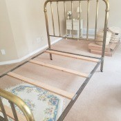 A brass bedframe with no mattress.