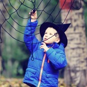 A child wearing a witch hat next to a yarn spiderweb.