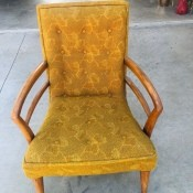 A vintage chair in upholstered in yellow-gold fabric.