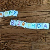 Painted Happy Birthday Banner - finished banner lying on the floor