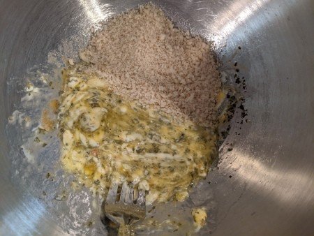 Adding bread crumbs to the egg mixture.