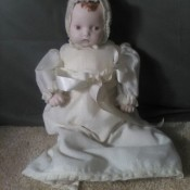 A bisque baby doll with brown hair.