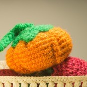 A crocheted pumpkin in a bowl.