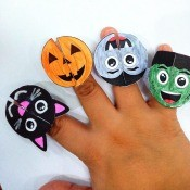 Paper Monster Rings - child's hand with a black cat, Jack 'o Lantern, vampire, and Frankenstein ring their fingers