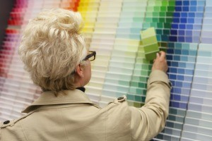 A woman looking at different color paint swatches.