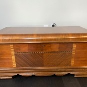A hope chest with an inlaid wood pattern.