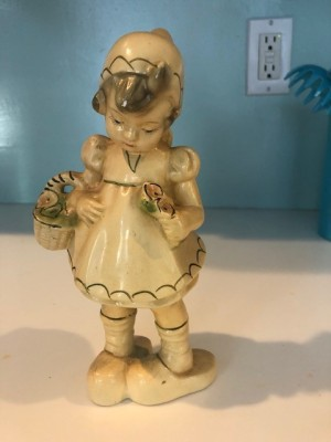 A ceramic figurine of a young girl with a basket.