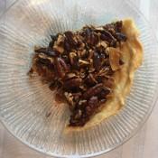 A slice of triple nut tart on a plate.