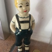A figurine with blonde hair and a green pants.