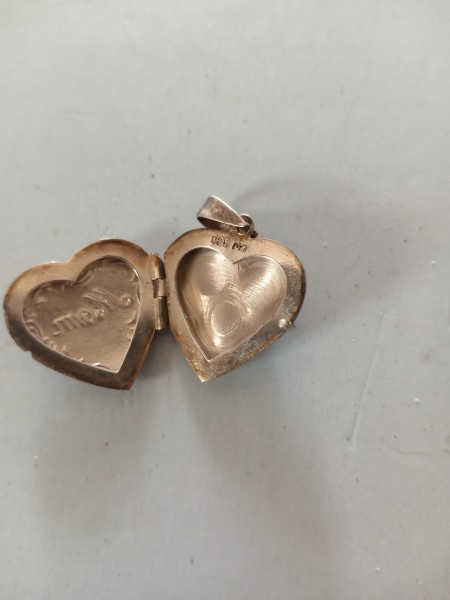 A metal locket with a marking inside.