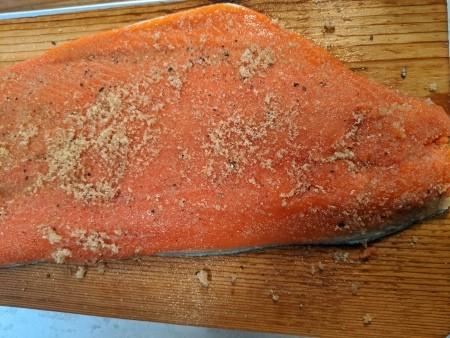 An uncooked salmon filet with seasonings on a cedar plank.