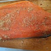 An uncooked salmon filet with seasonings on a cedar plank.