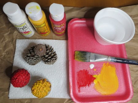 A tray with paint and a brush next to pine cones.