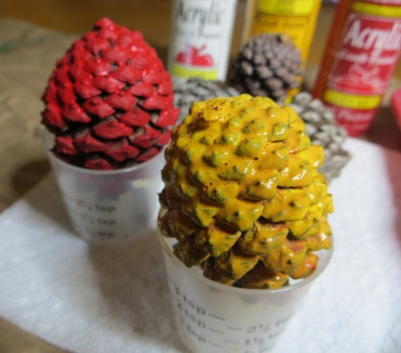 Pine cones in plastic medicine cups, painted red or yellow.