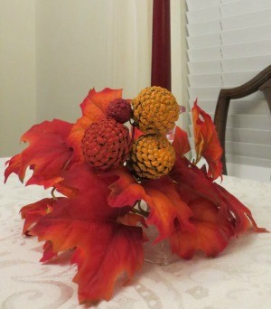 A candle arrangement with fall leaves and painted pinecone zinnias.