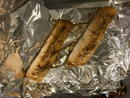 Two cooked salmon filets on aluminum foil.