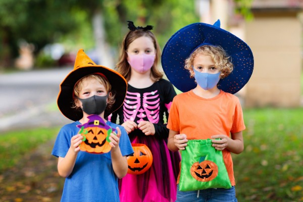 Three trick-or-treaters in COVID masks.