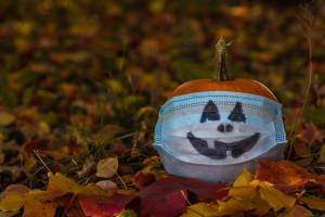 A pumpkin wearing a mask with a jack-'o'-lantern face.