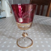 A footed glass with cranberry coloring and gold trim.