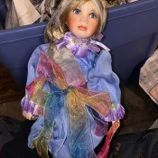 A porcelain doll wearing a colorful outfit.