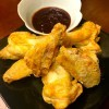 A plate of crispy bat wings with dipping sauce.