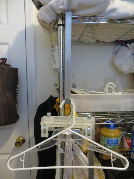 A wreath hanger holding up laundry hangers on a shelf.