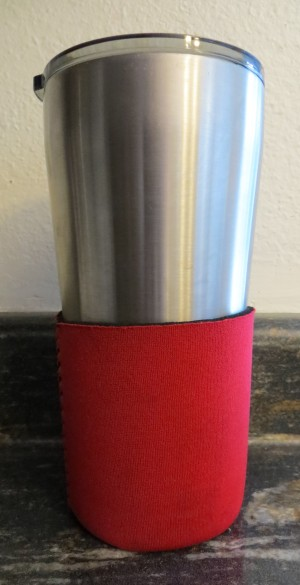A travel mug with a foam koozie at the bottom.