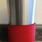 A travel mug with a foam koozie at the bottom.