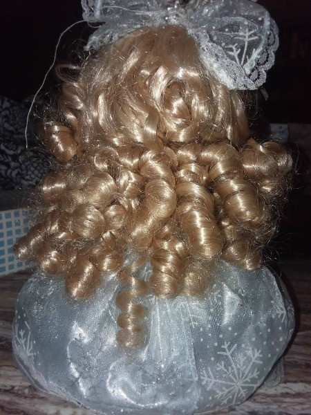 The back of a doll with curly blonde hair.