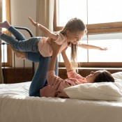 A mom flying her child above her on a bed.