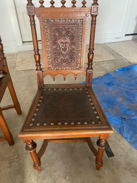 An ornate wooden chair with a leather seat.
