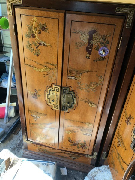 A wooden armoire with decorative paintings.