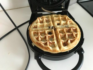A cooked waffle in the waffle maker.