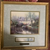A Thomas Kinkade print in a official gold frame.