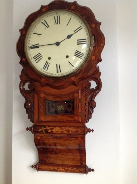 A wall mounted clock with chimes.