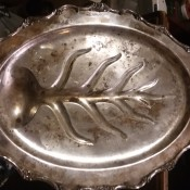 A silver tray with a leaf pattern in the center.